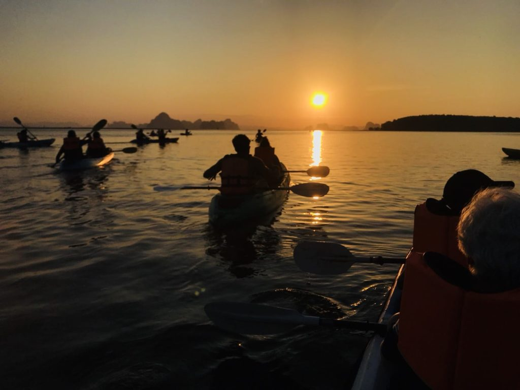 a group of kayakers at sunset
