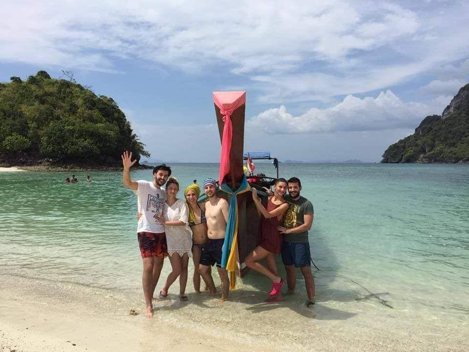 group of friends with a longtail boat at an island