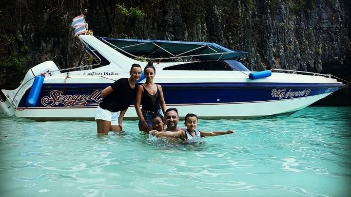 a family swimming near a moored speedboat