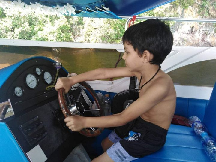 a young boy at the steering wheel of a speedboat