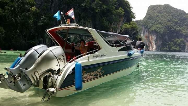 a small speedboat moored at a beach in clear water