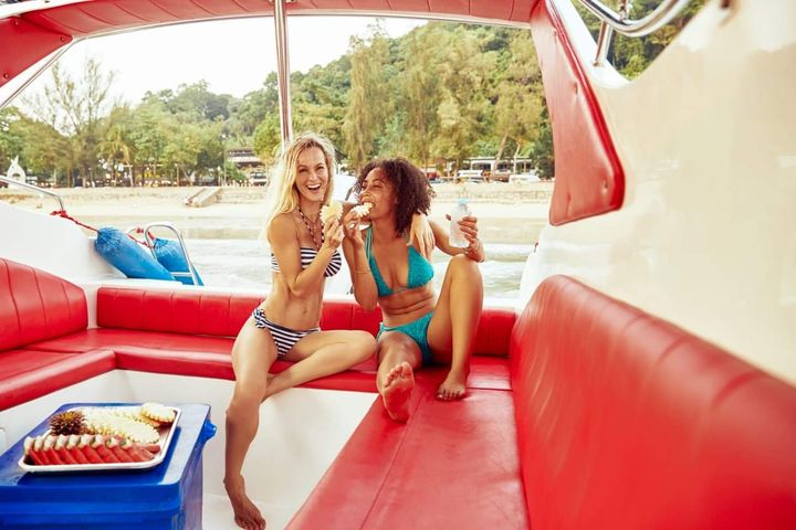 two women eating fruit on a speedboat
