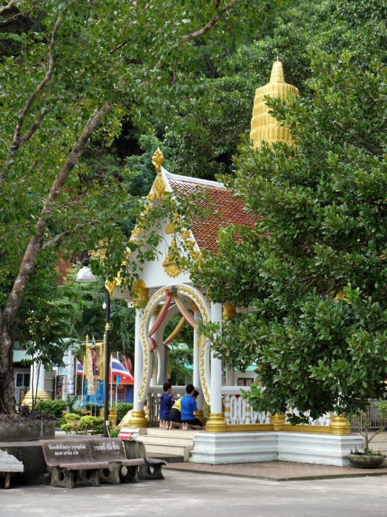 people praying at a small temple in Thailand