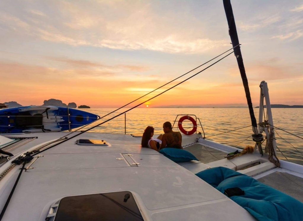 a couple on a catamaran yacht at sunset