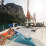 a couple relaxing and a boat crew on a catamaran sailing yacht