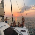 a group of people on a catamaran yacht at sunset