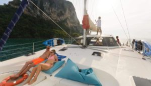 a couple relax on the deck of a sailing catamaran